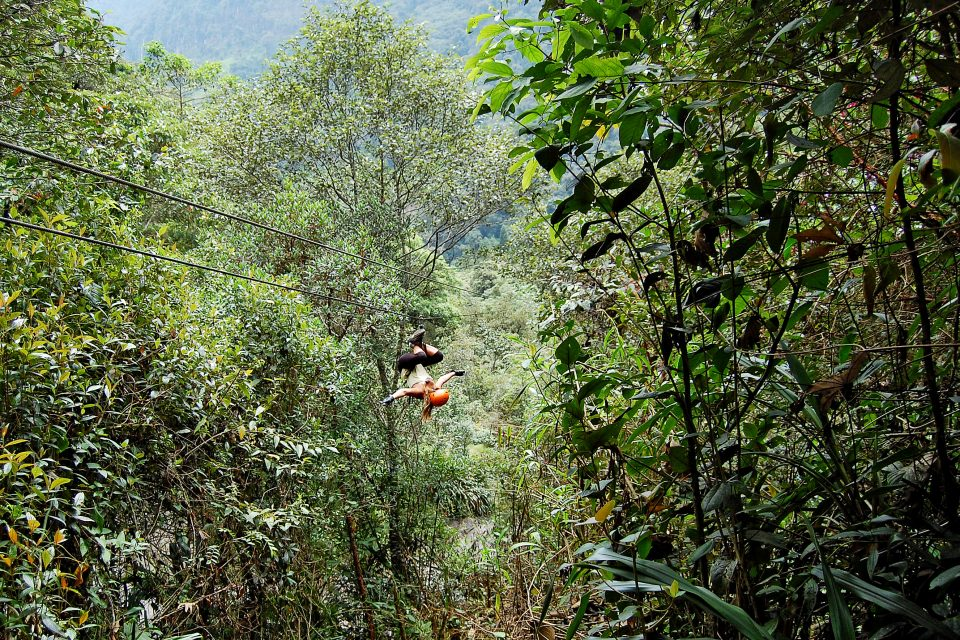 A woman ziplining upside down through the jungle