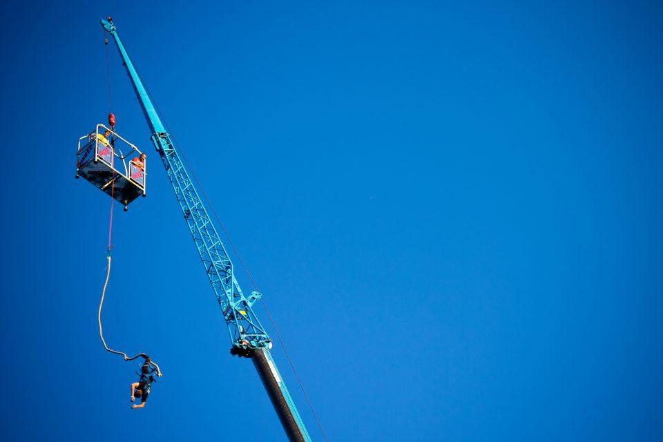 Man bungee jumping off a crane