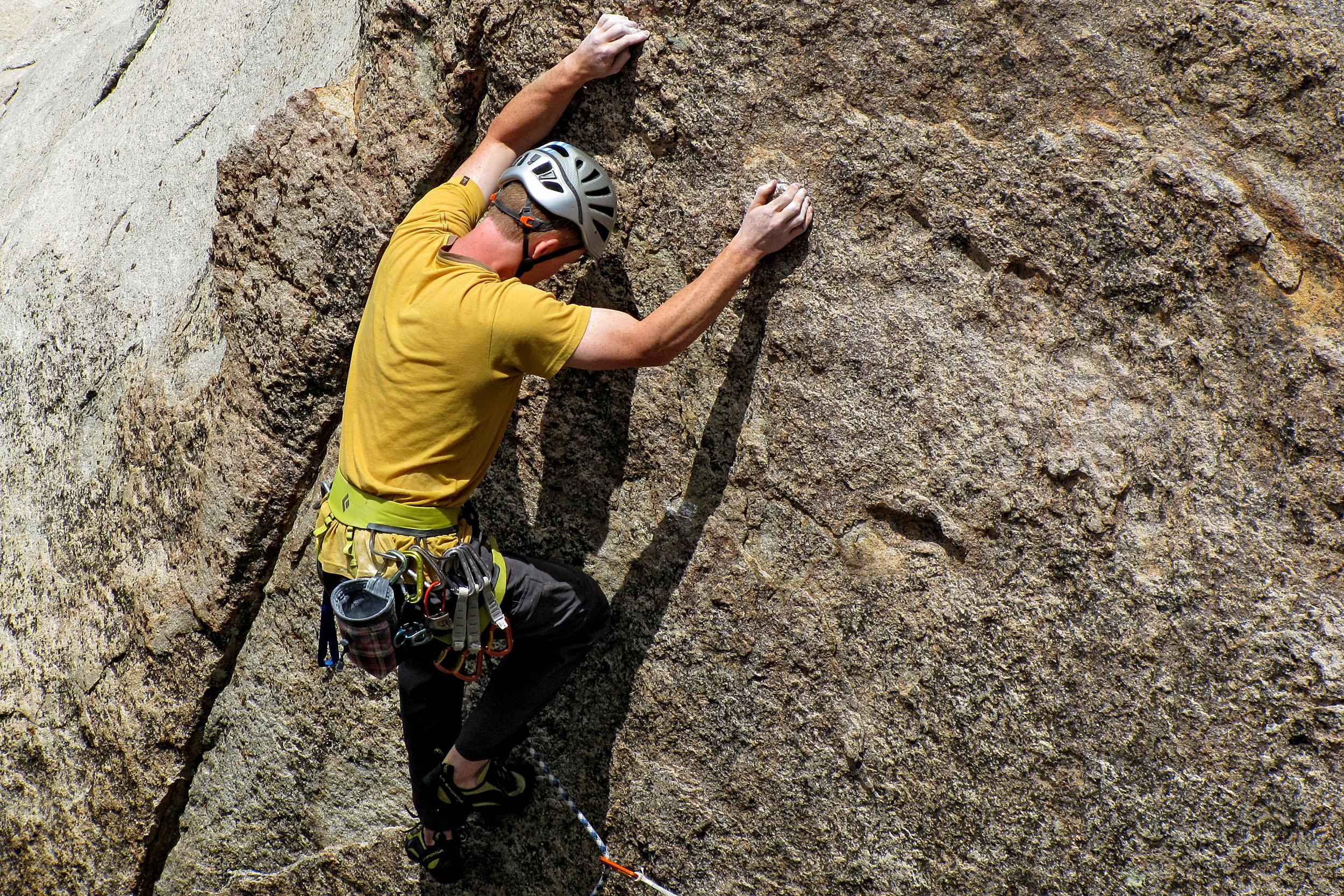 man rock climbing wall