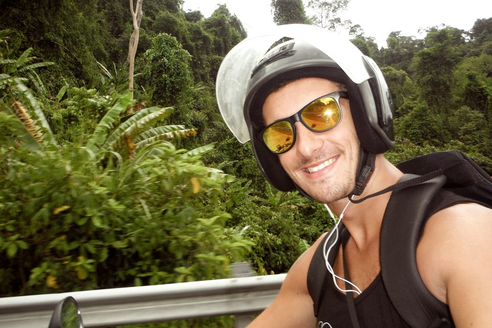 A close up of a man wearing his motobike helmet