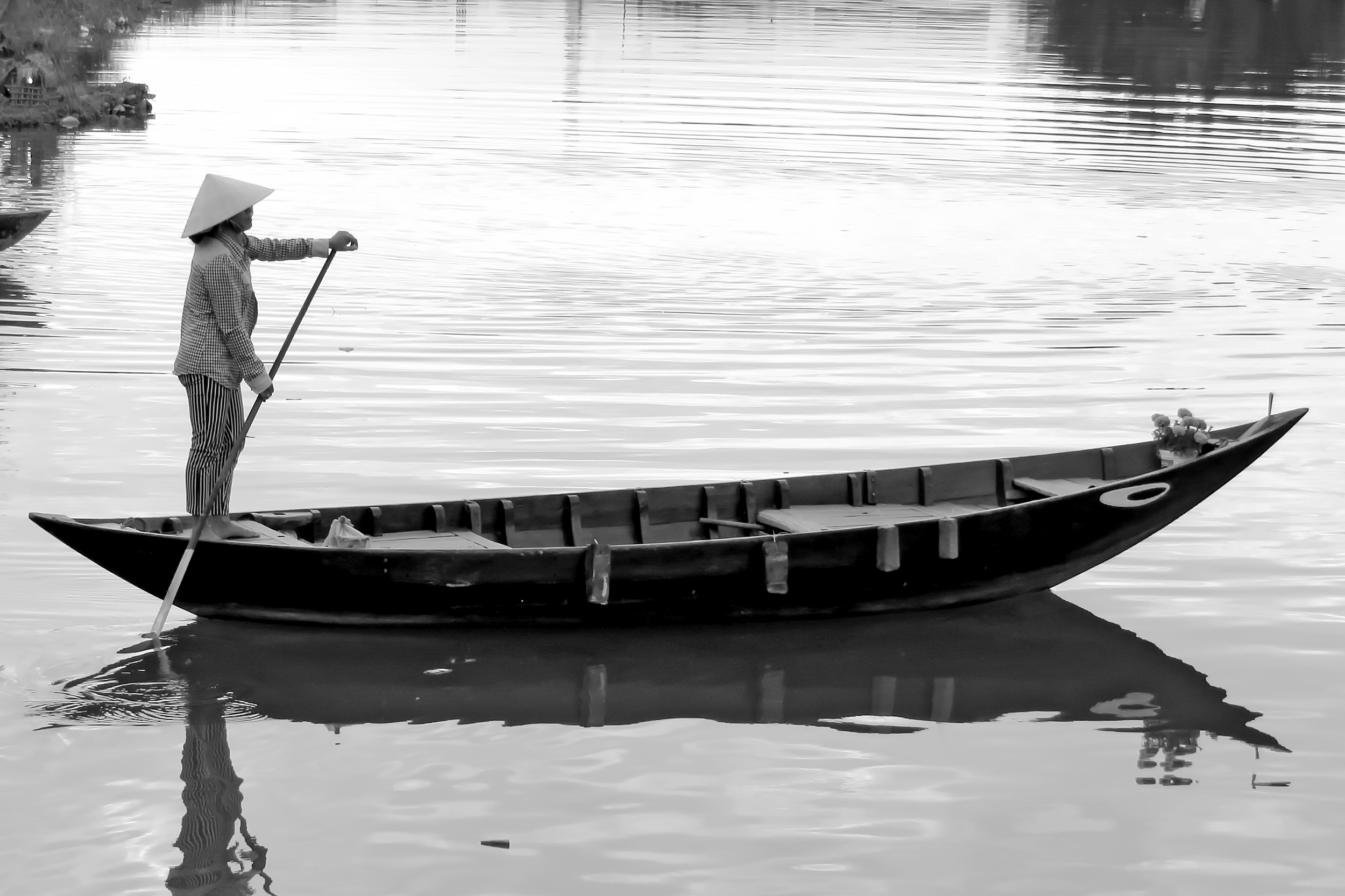 A woman punting a canoe