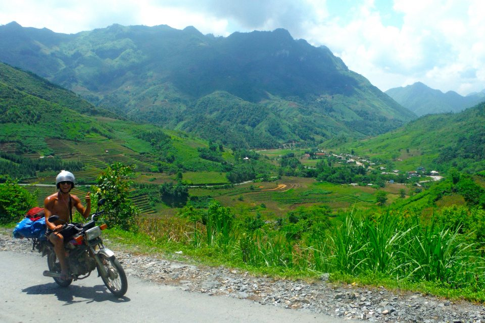 A man sat on a motorbike in front of mountains