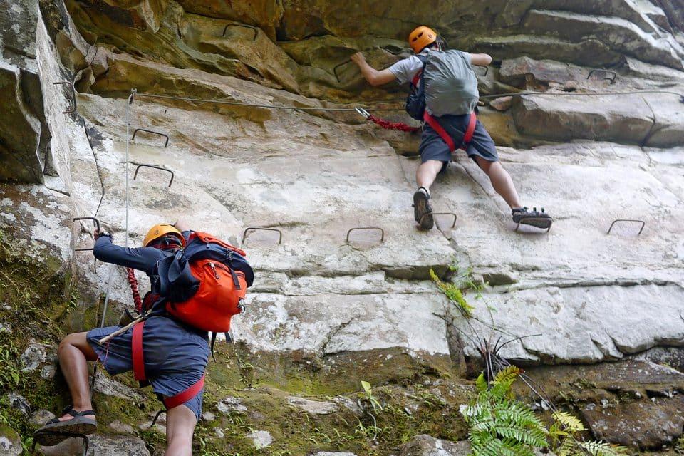 man climbing rocks laos