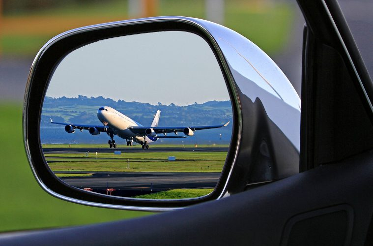 A view of a plane taking off in a car's side mirror
