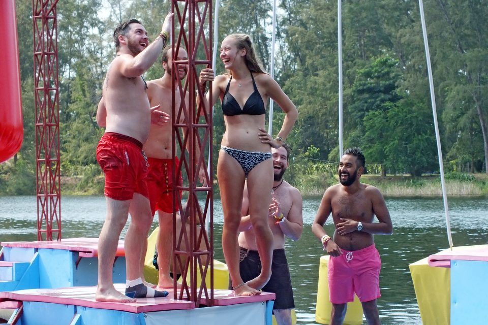 A group of people standing on a floating assault course laughing