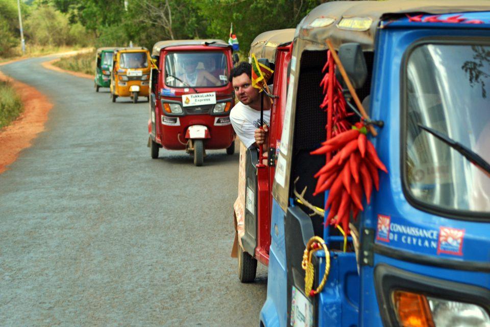 People driving tuk tuks on the road