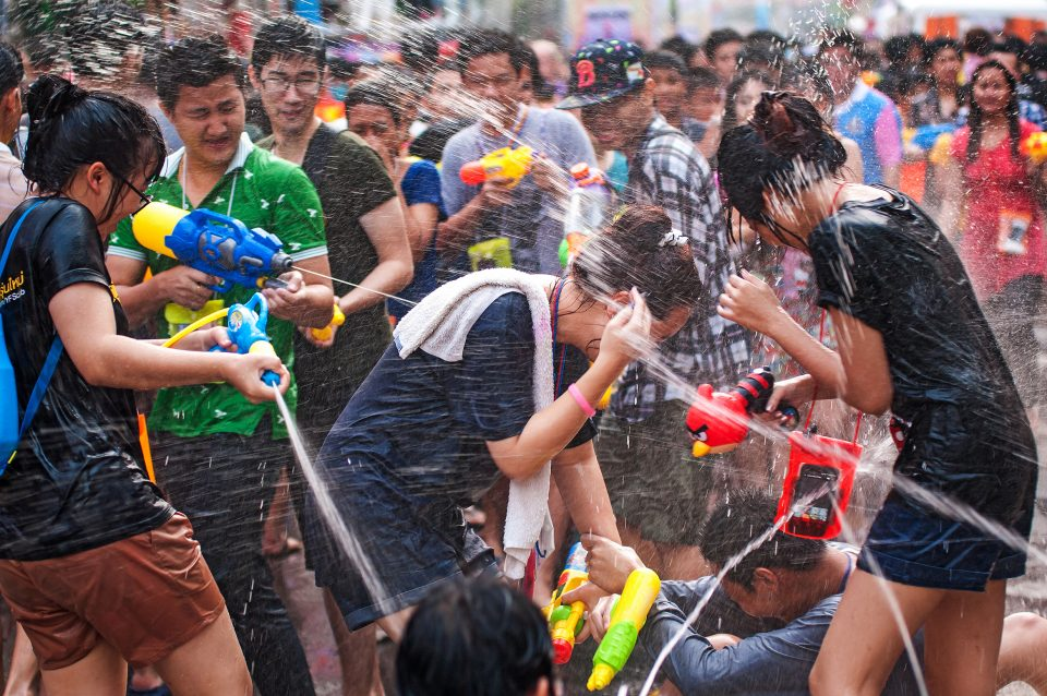 Groups of people squirting each other with water guns