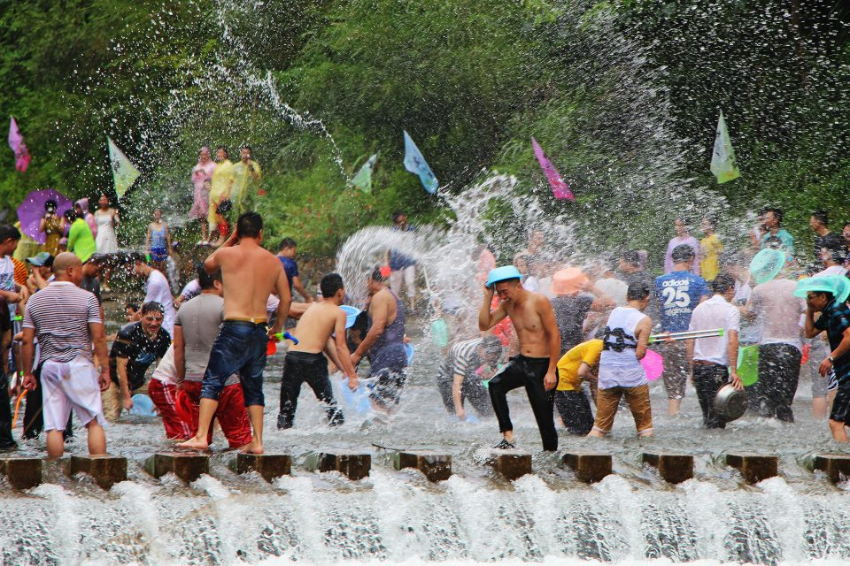 A group of people dancing in water fountains