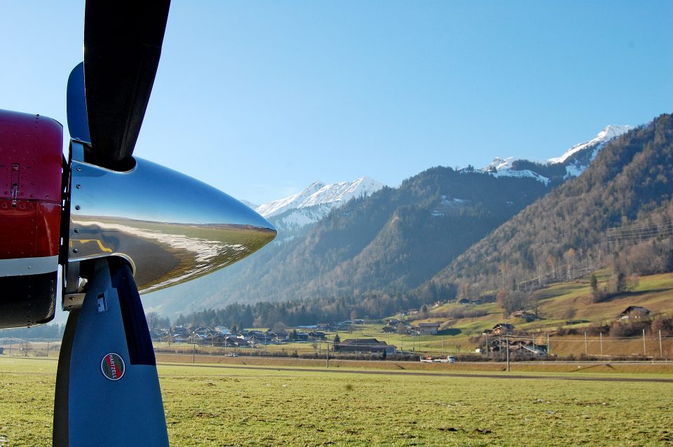 Side shot of a plane propeller and mountains behind