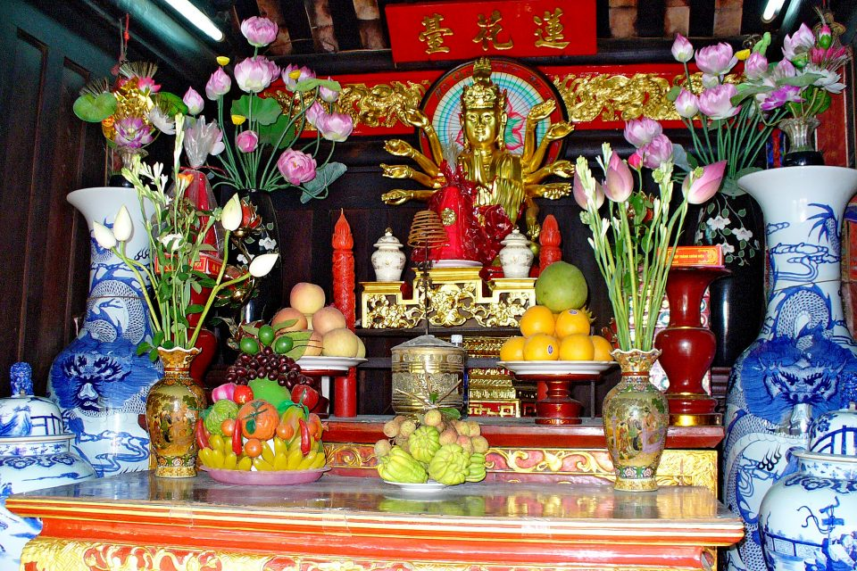 A golden buddha with bowls of fruit as offerings