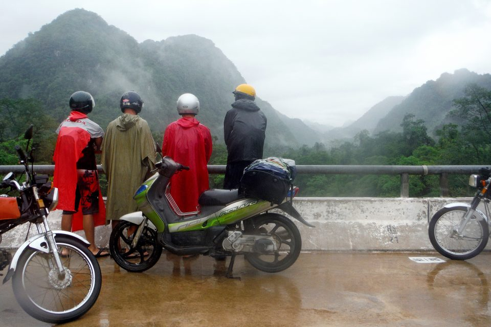 A group of riders looking at mountains in the rain