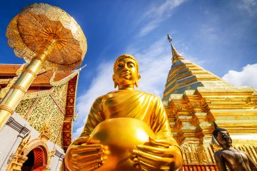 Upwards view of a golden buddha and temple