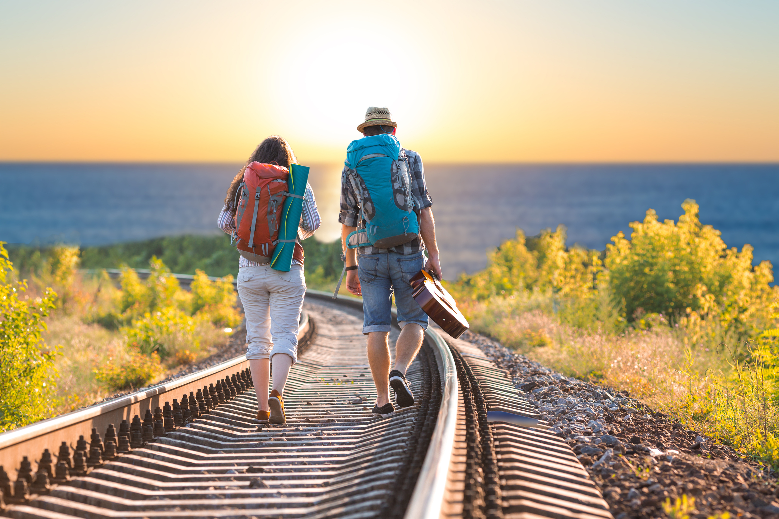 A couple backpacking down a train track