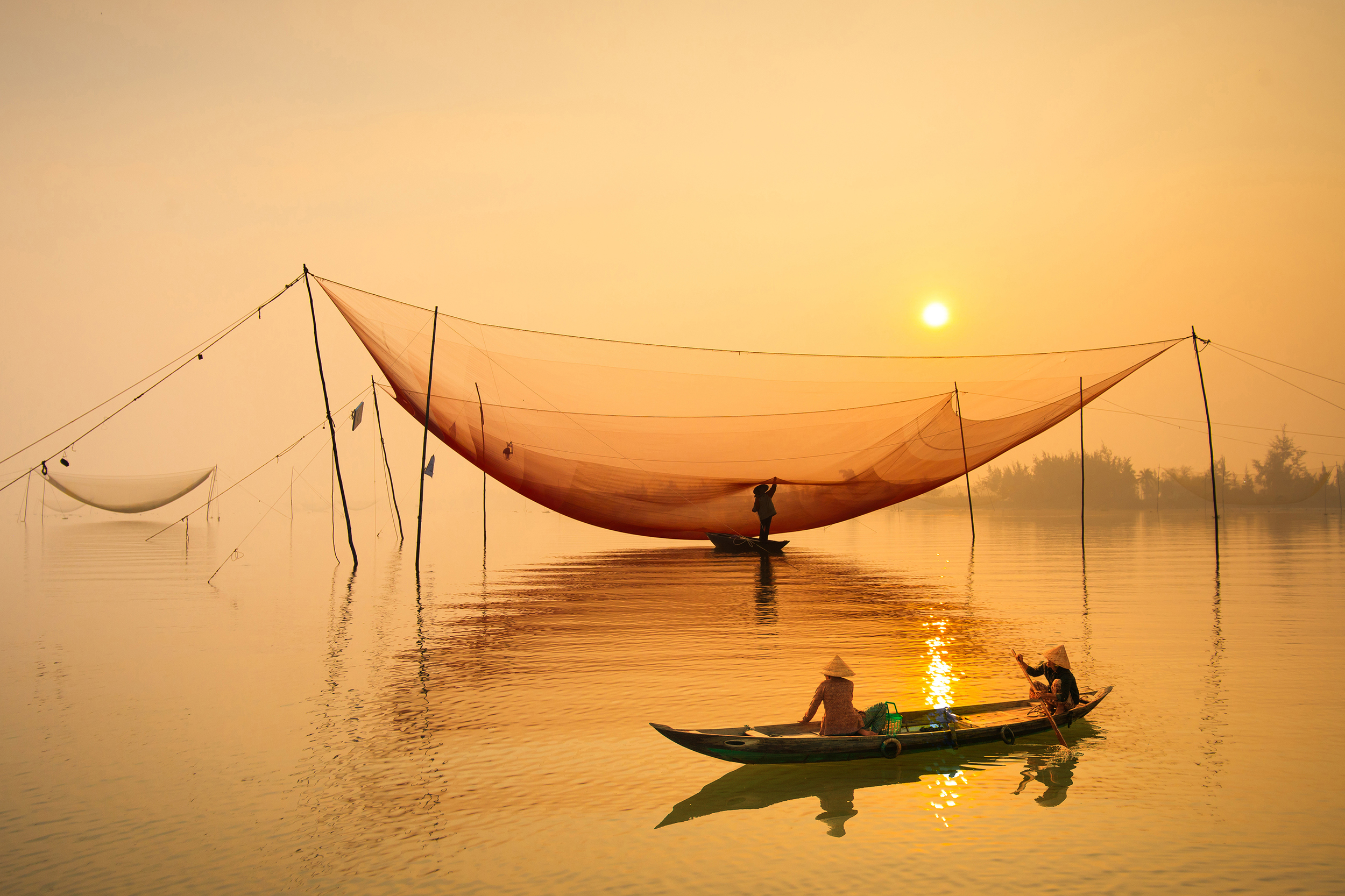 Two local people fishing from a canoe at sunset