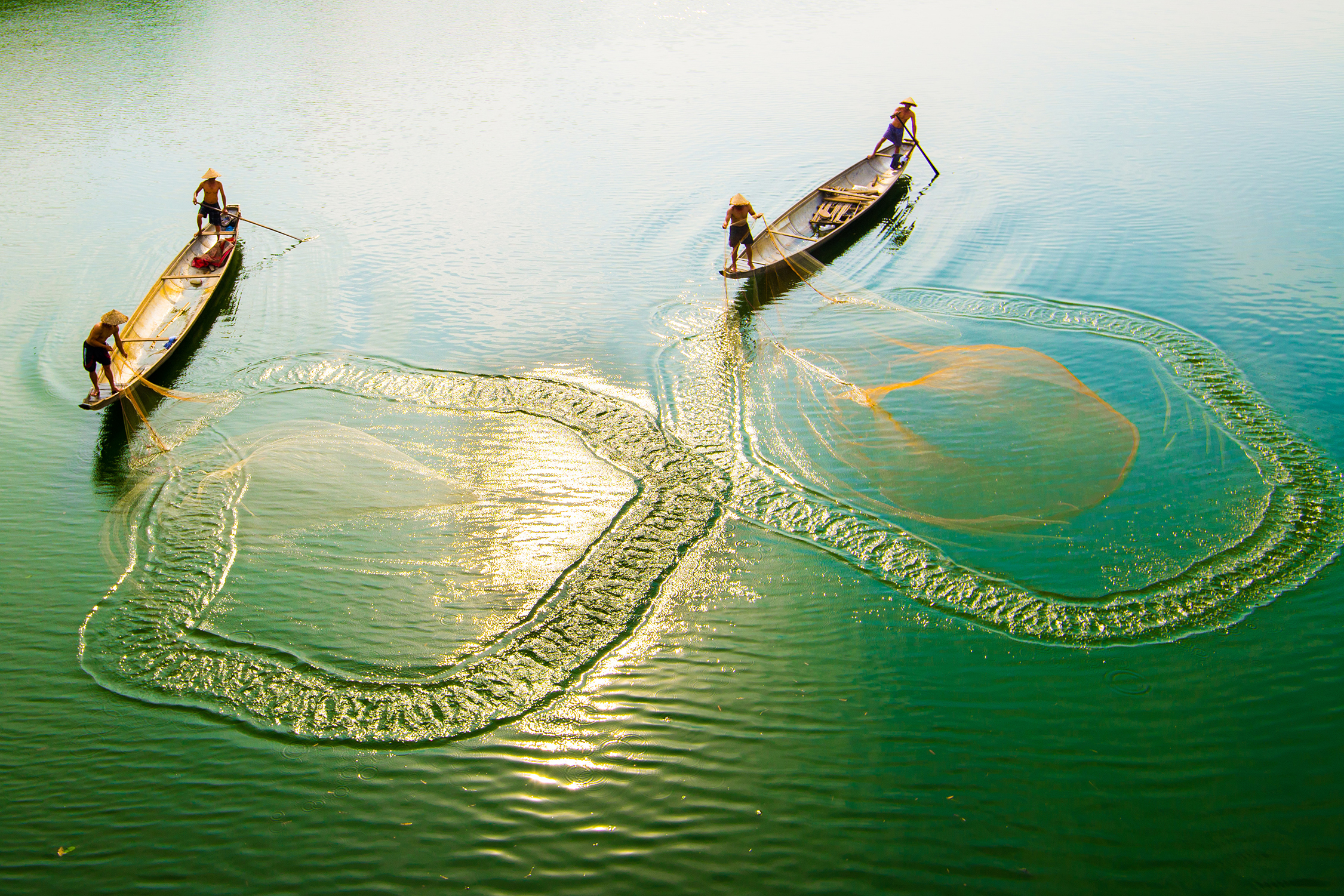 Local people casting fishing nets from their canoes