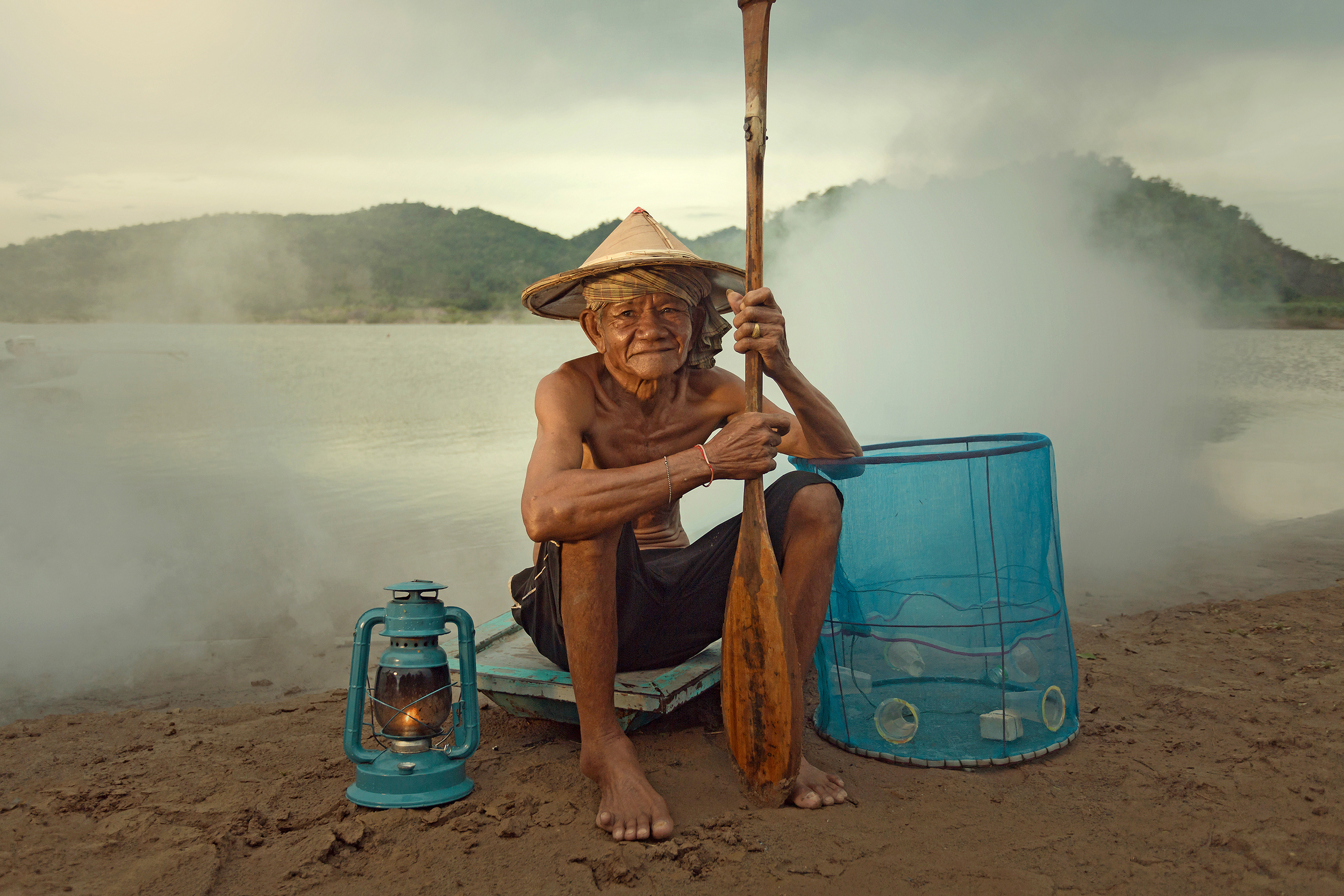 A local fisherman sitting on the ground