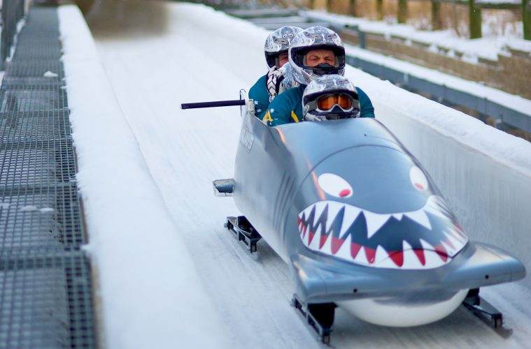 Three men in a bobsleigh on a course