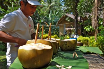 A local man preparing coconut drinks