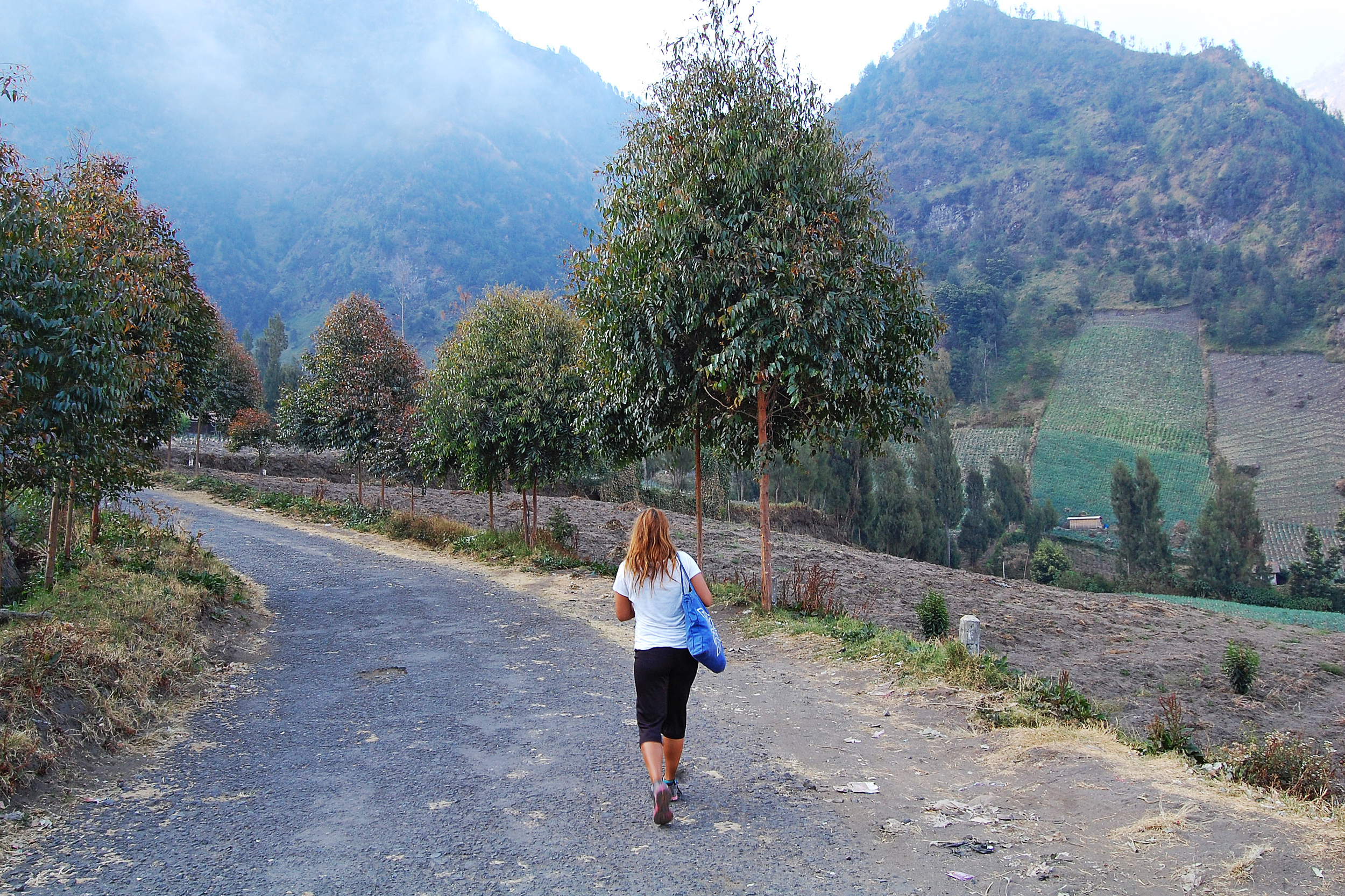A woman walking down a road on the mountain