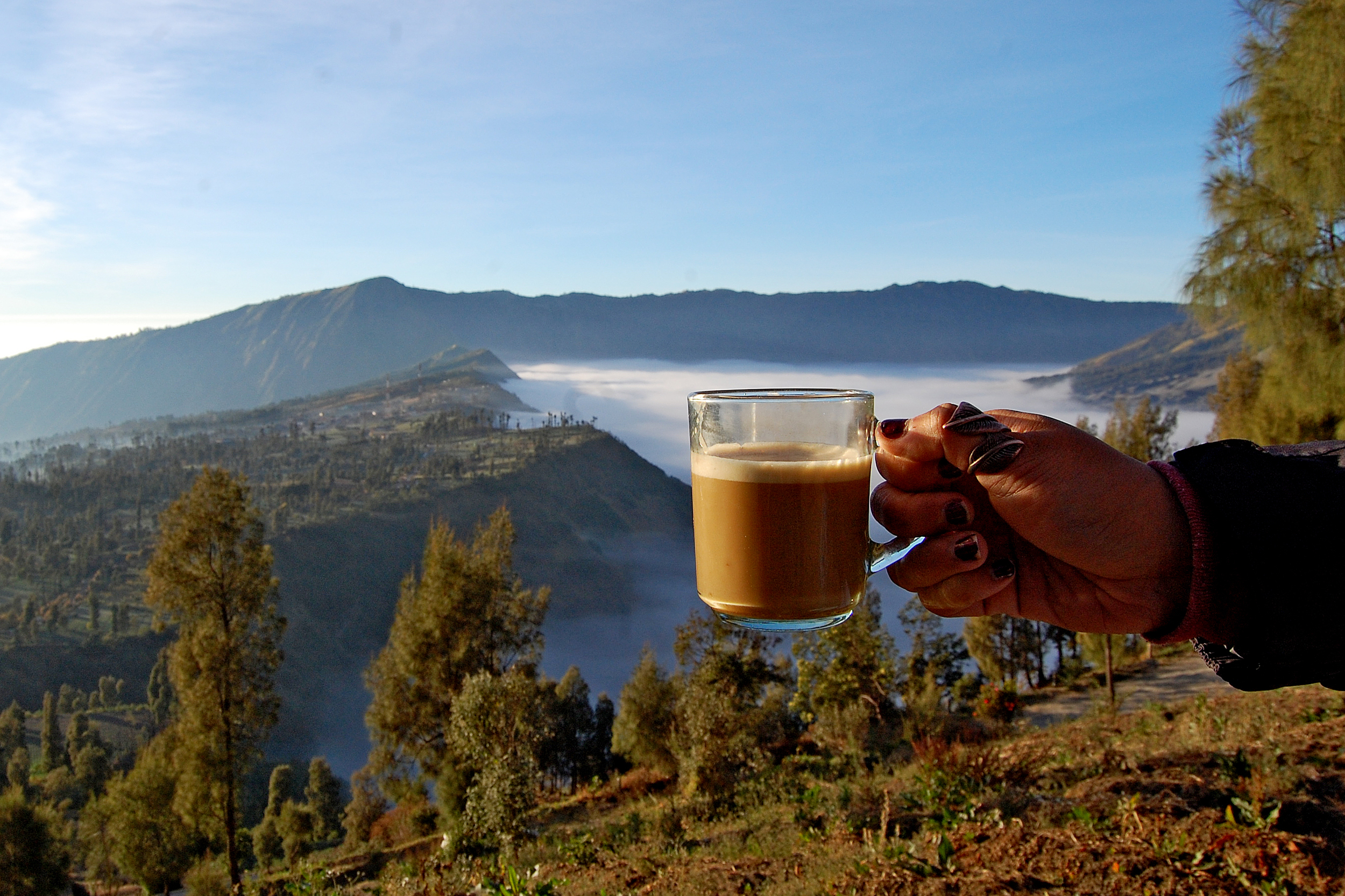 A cup of coffee in front of mountain views through the clouds