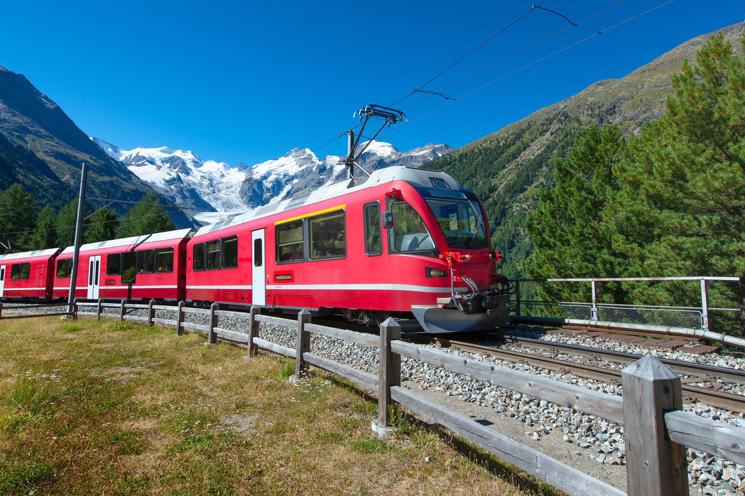 A red train through the mountains
