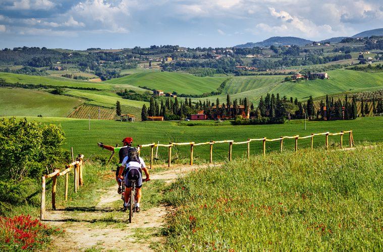 Two cyclers biking through fields