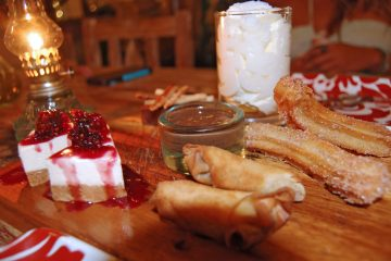 Close up of a desert platter with churros and cheesecake