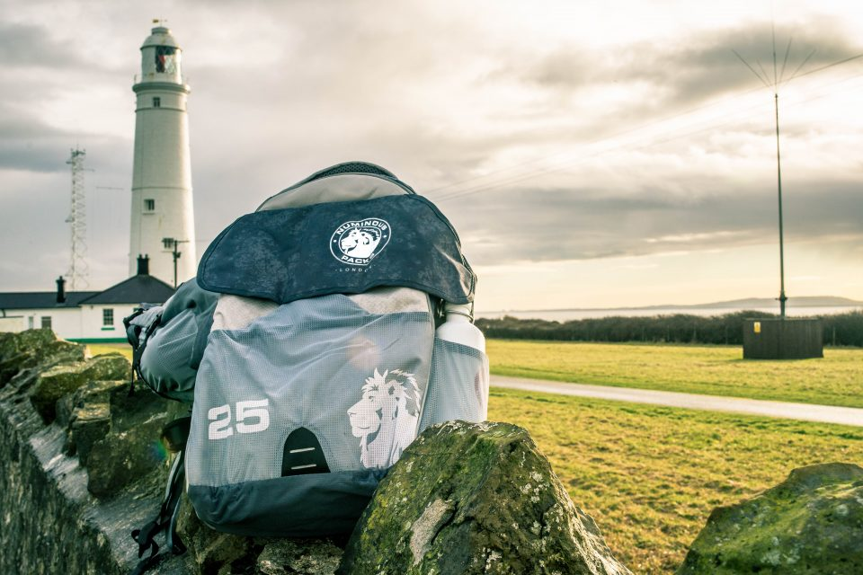 Close up of a backpack with a lighthouse behind