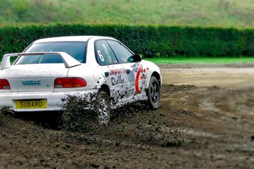 A rally car skidding around a mud track