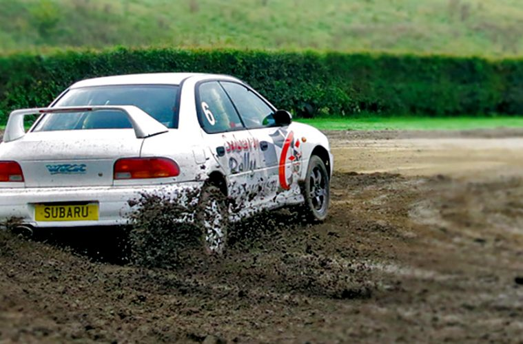 A rally car skidding around a mud track