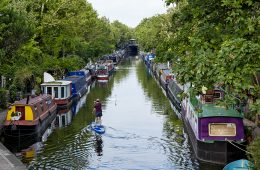 A man paddle boarding down a canal