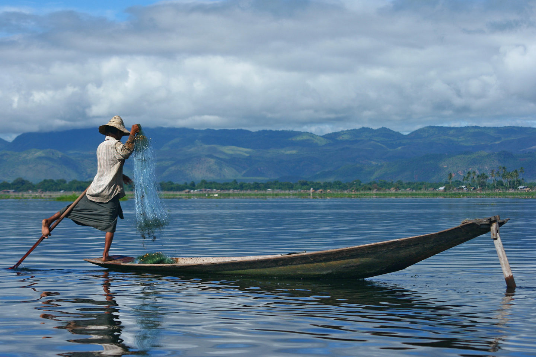 A man fishing off a canoe