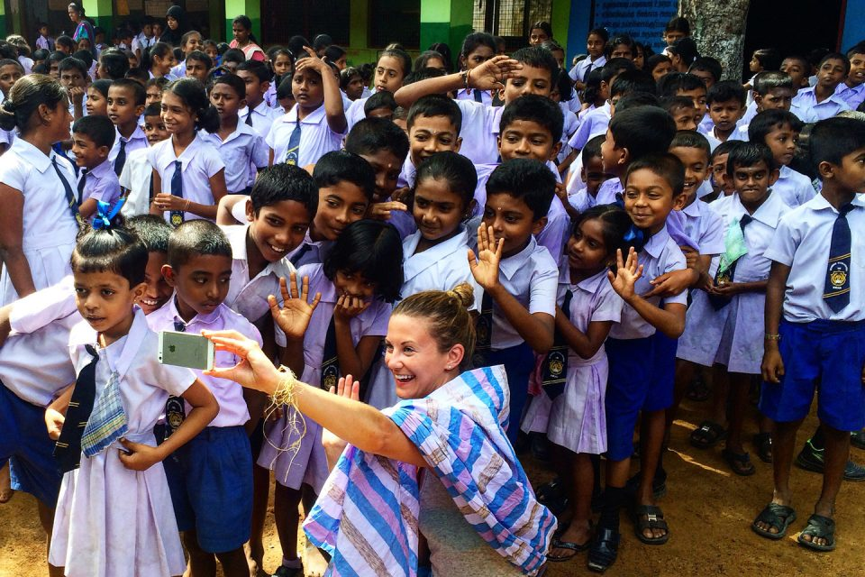 Taking a selfie with a group of kids on the Lanka Challenge