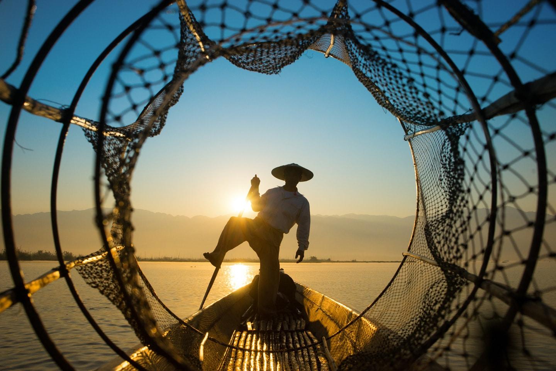 Fisherman shot through a net in Myanmar