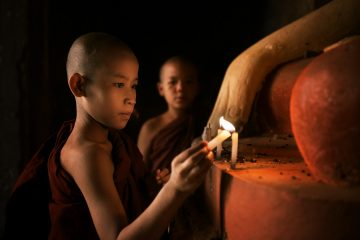 Small child lights a candle in Myanmar