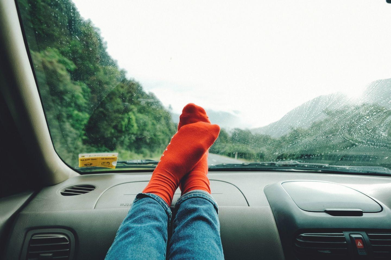 on a roadtrip feet in dashboard