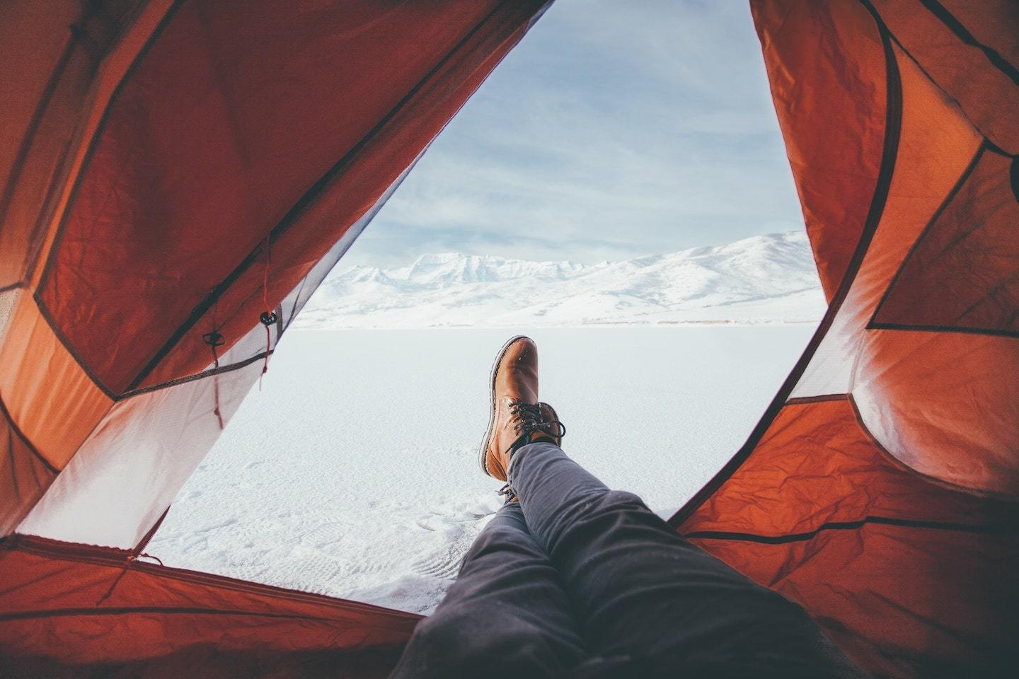 man in tent with snow outside