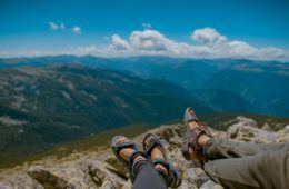 Two people sitting on top of a mountain in sandals