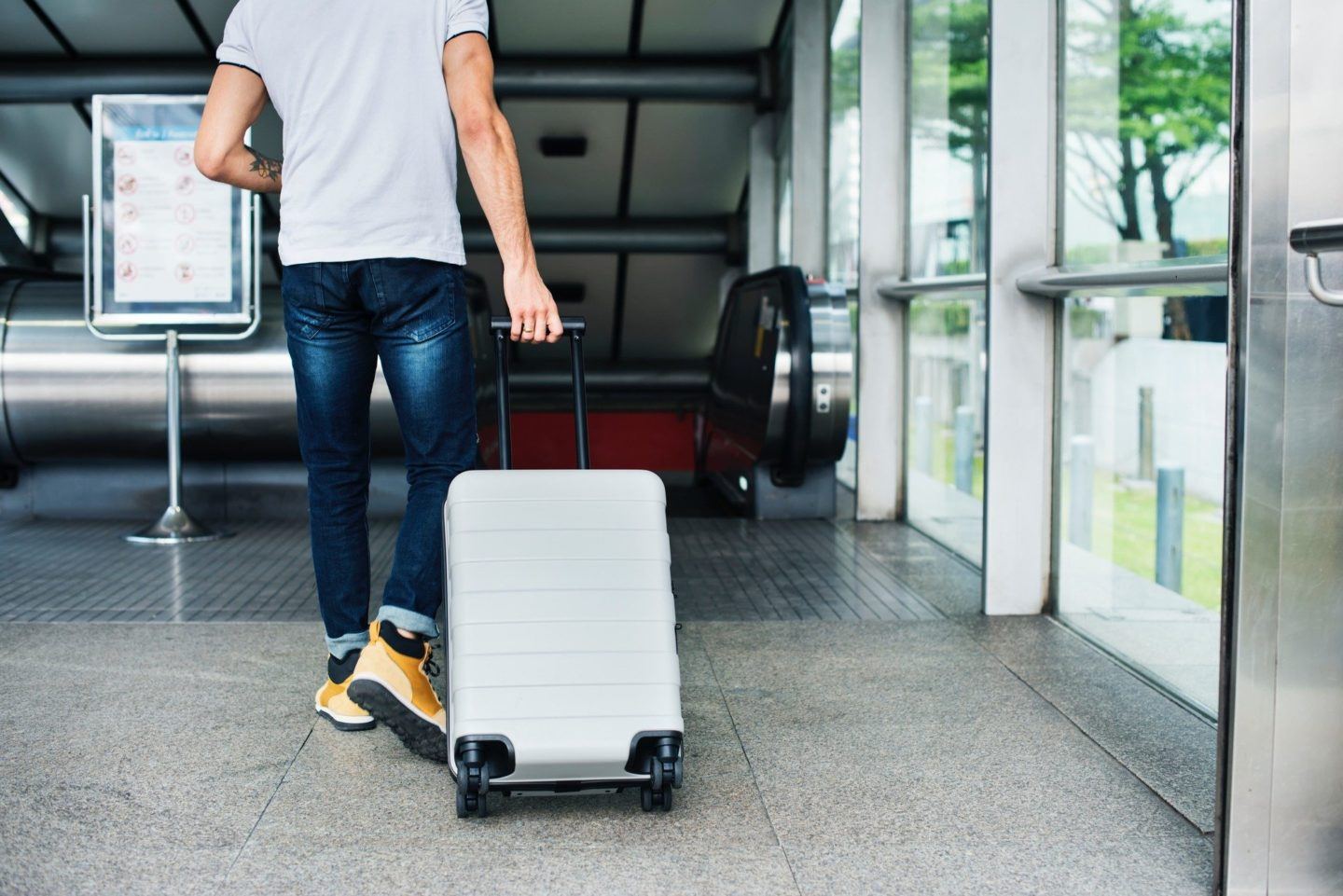 Man rolling hard shell carry-on bag