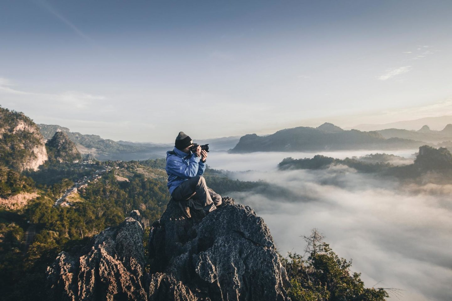 person taking photo sitting on rock in the mountains