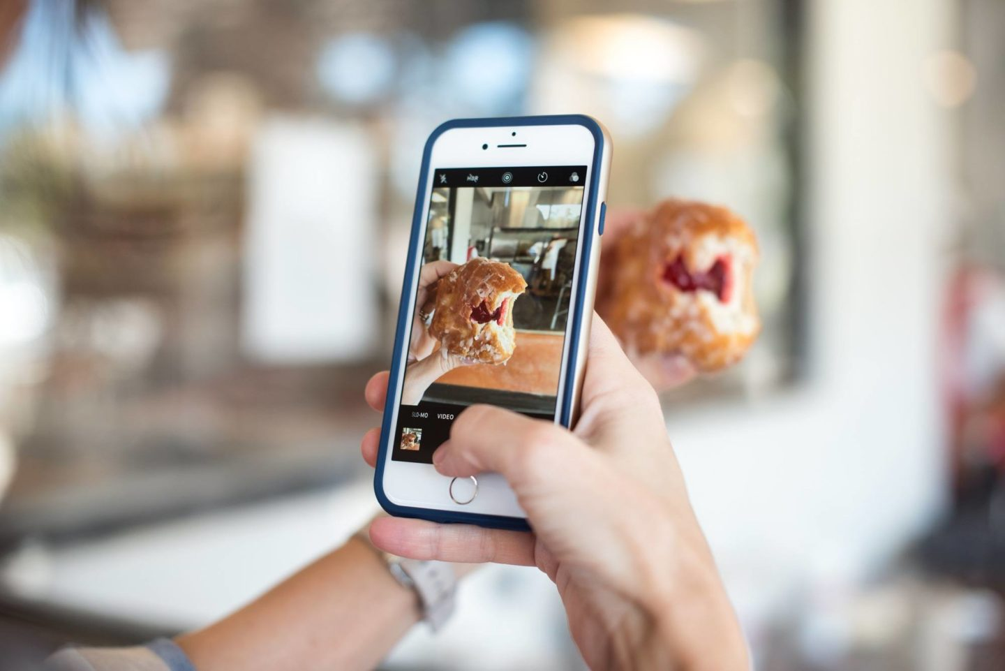 person taking photo with iphone of doughnut