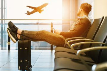 Man watching airplane with feet on luggage
