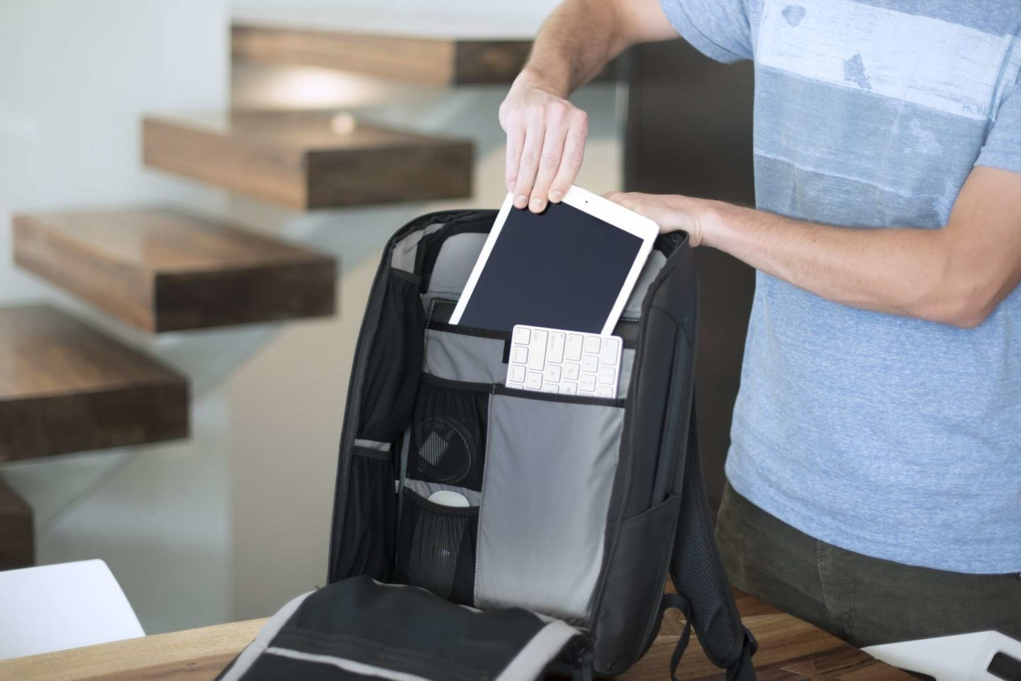 Person sliding tablet into backpack