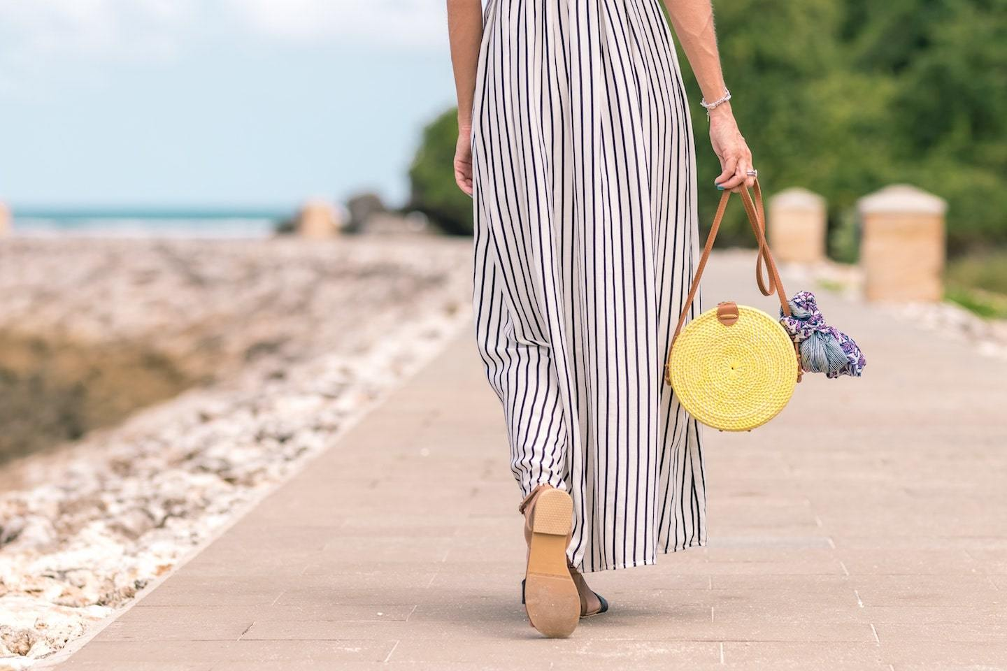 woman walking on boardwalk with bag