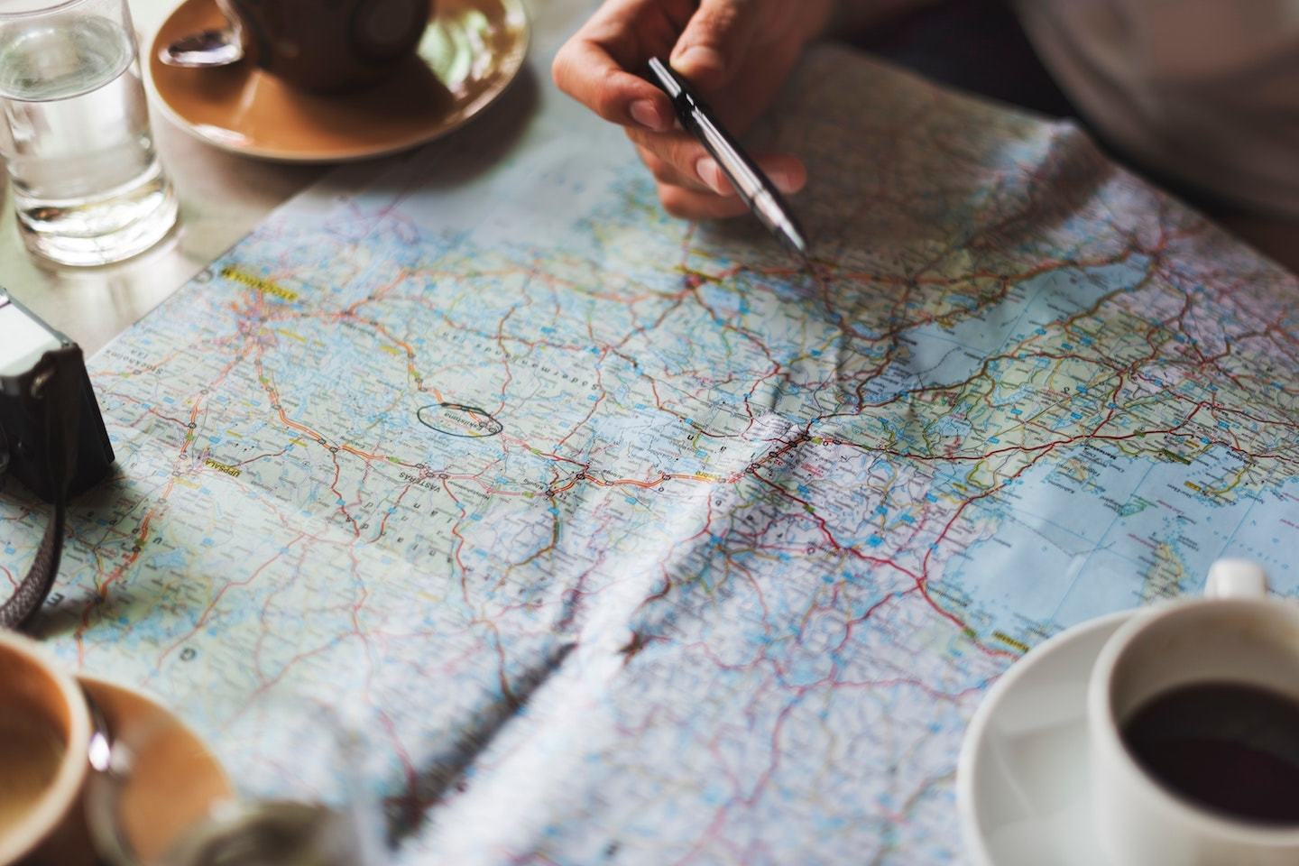 a person holding a pen over a map with coffee