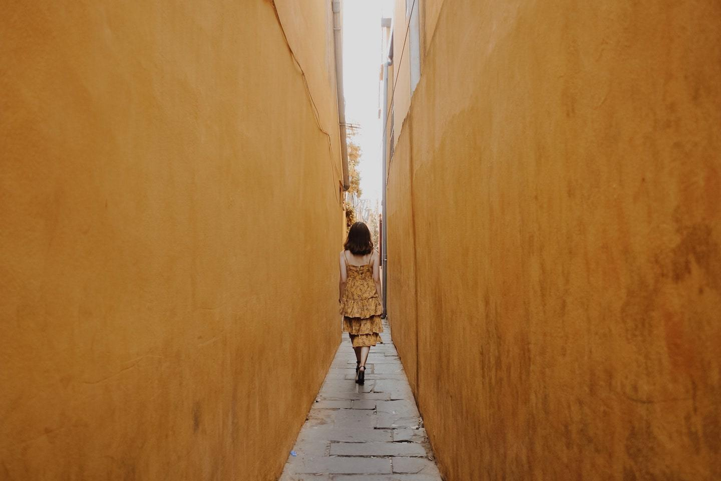 woman walking in alley