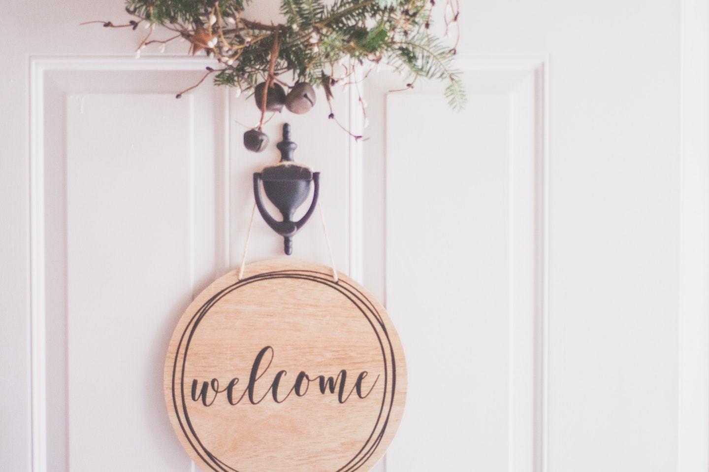 welcome sign hanging on front door