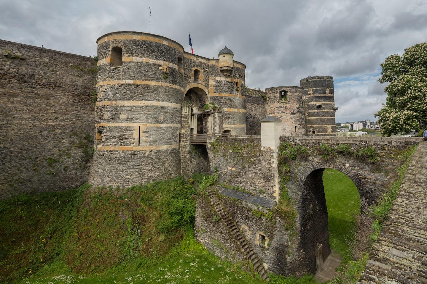 castle in france with curved towers and bridge