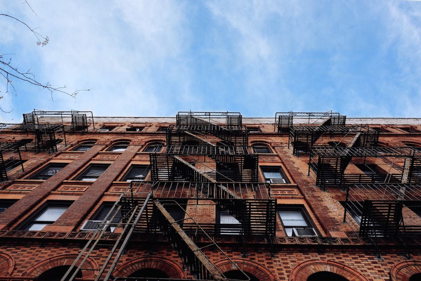 upward view of brick apartments and sky