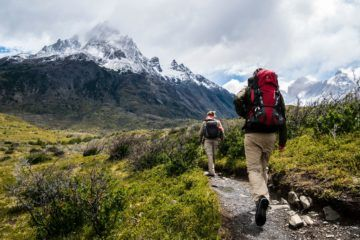 Man hiking a trail in mountains wearing backpack